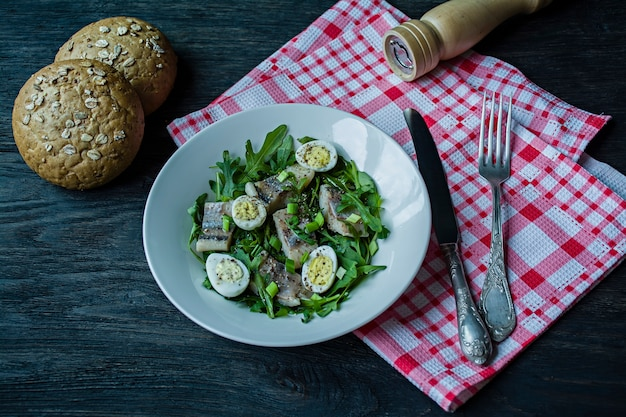 Marinierter hering mit rucola, zwiebeln, gekochten wachteleiern, zitronensaft und olivenöl.
