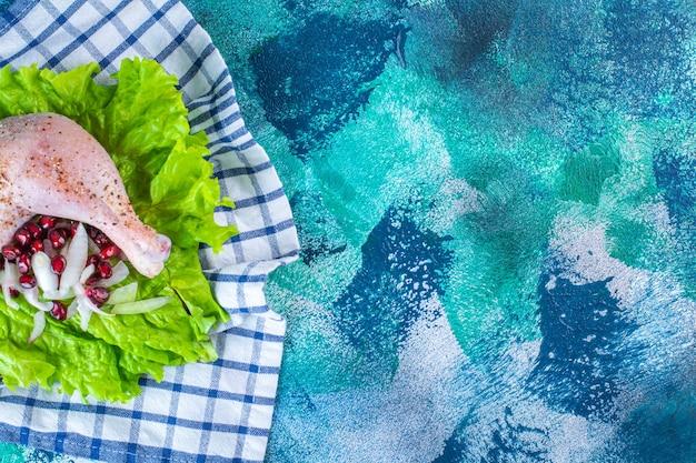 Marinierter hühnertrommelstock mit granatapfelkernen auf salatblättern auf einem brett auf einem geschirrtuch auf blauem hintergrund. foto in hoher qualität