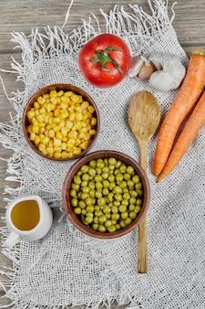 Marinierter mais und grüne erbsenbohnen in holzbechern.
