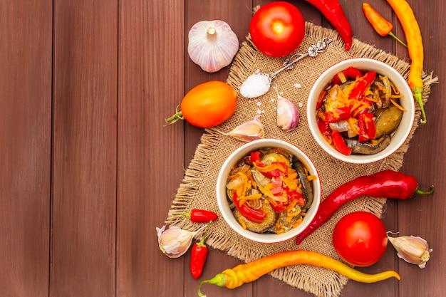 Marinierter salat mit eingelegtem gemüse: auberginen, karotten, paprika, tomaten, knoblauch