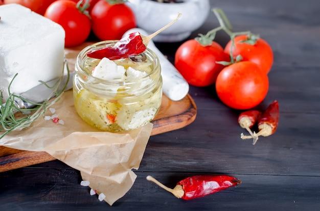 Marinierter würziger feta in einem glas und gemüse für salat.