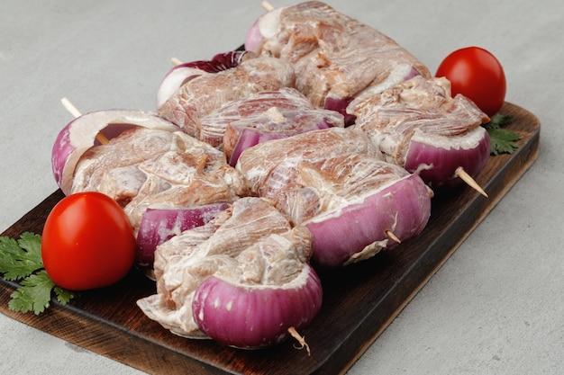 Mariniertes fleisch am spieß mit zwiebeln auf grauem tisch