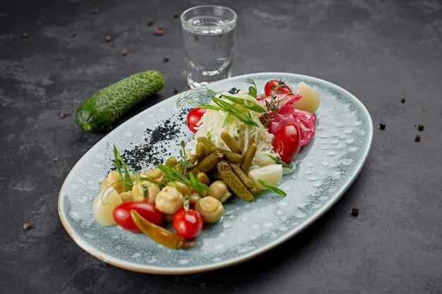 Mariniertes gemüse mit pilzen und einem glas wodka