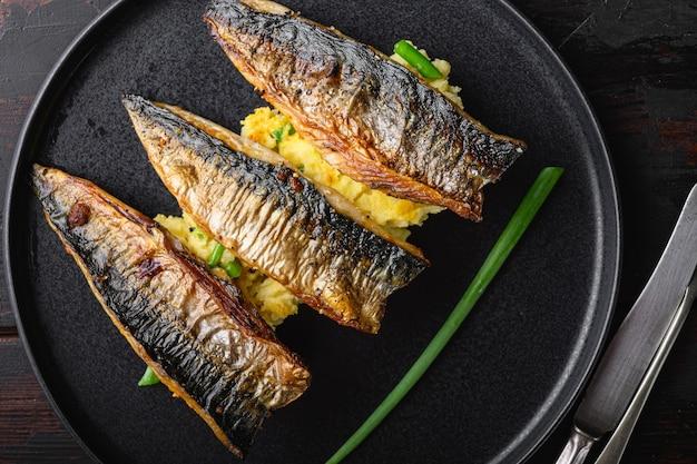 Mariniertes makrelengericht mit kartoffelpüree auf dunklem holztisch, flach gelegt