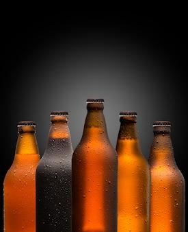 Marken- und marketingkonzept für bier mit einer reihe von ungeöffneten, unbeschrifteten, leeren, leeren, braunen flaschen auf einem dunklen, schattigen hintergrund, der das oktoberfest oder das nachtleben vorstellt