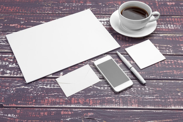 Markenbriefpapier auf purpurrotem schreibtisch. draufsicht des papiers, der visitenkarte, der auflage, der stifte und des kaffees.