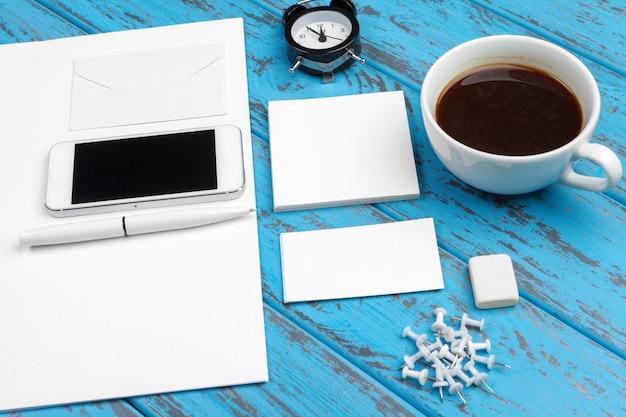 Markenbriefpapiermodell auf blauem schreibtisch. draufsicht des papiers, der visitenkarte, der auflage, der stifte und des kaffees.