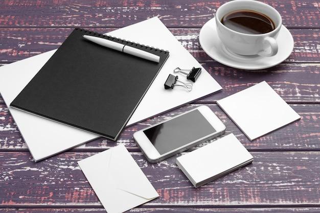 Markenbriefpapiermodell auf purpurrotem schreibtisch. draufsicht des papiers, der visitenkarte, der auflage, der stifte und des kaffees.