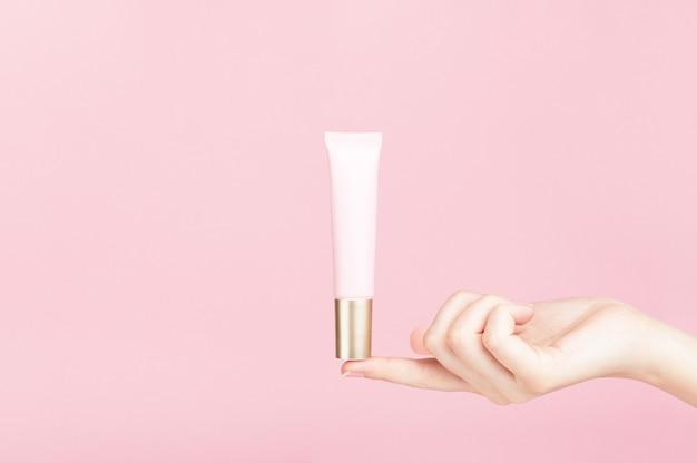Markenloser flakon am weiblichen finger. plastiktube für creme, körperlotion, toilettenartikel.