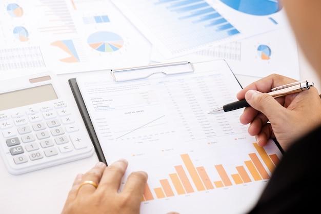 Marketing-performance-analyst arbeitet mit verkauf bericht auf einem schreibtisch
