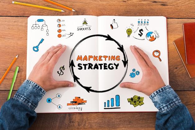 Marketingstrategie planen. nahaufnahme eines mannes, der hände auf seinem notizbuch mit bunten skizzen hält, während er am holzschreibtisch sitzt
