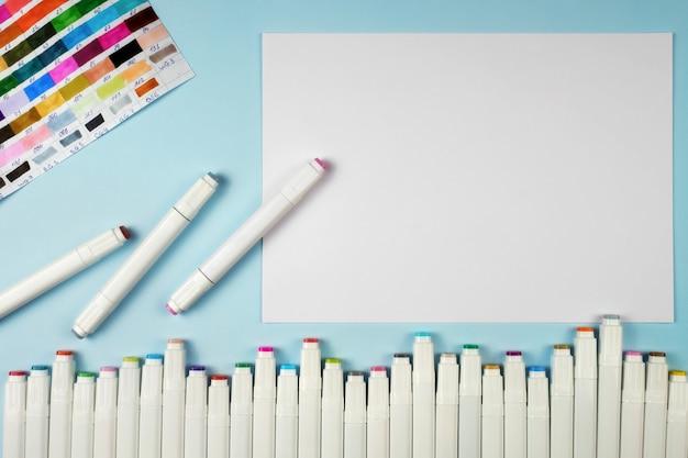 Markierungen zum zeichnen und ein weißes blatt papier auf einem blauen hintergrund.