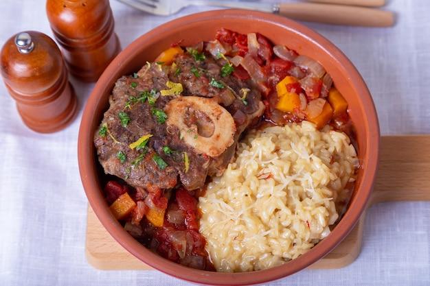 Markknochen. kalbshaxen mit safranrisotto in mailand, gremolata und sauce. traditionelles italienisches gericht.