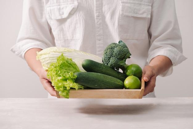 Markt. gesundes veganes essen. frisches gemüse, beeren, grüns und früchte im holztablett: gurkenrettichgrüne erbsen ... weißer tisch. in den händen des mannes kopienraum