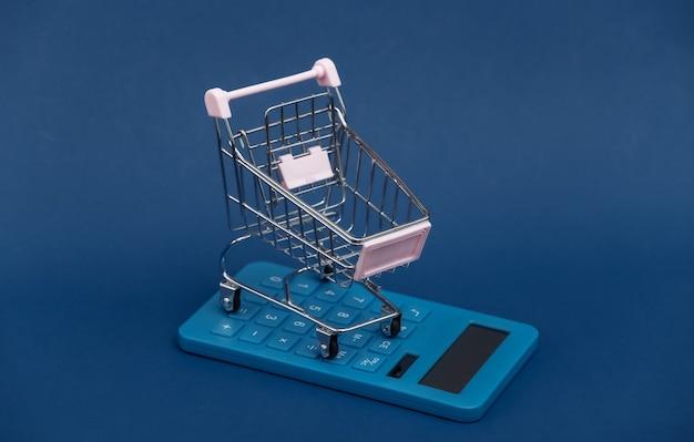 Marktkosten. mini-einkaufswagen mit taschenrechner auf klassischem blauem hintergrund