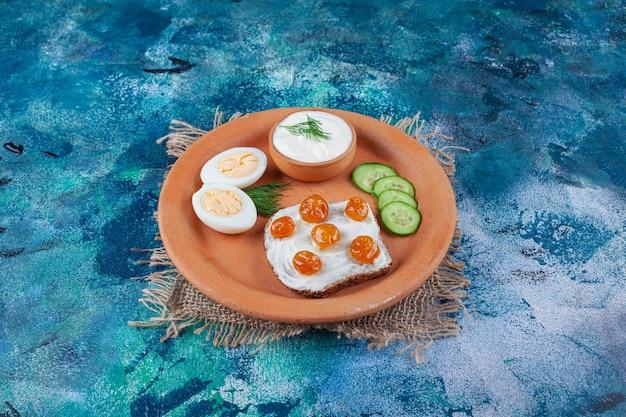 Marmelade auf geschnittenem brot neben geschnittenem ei, gurke auf einem teller auf leinenserviette auf dem blauen tisch.