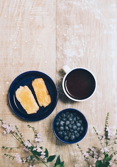 Marmelade auf toast verteilen; blaubeeren; kaffeetasse und rosa blumen auf holztisch