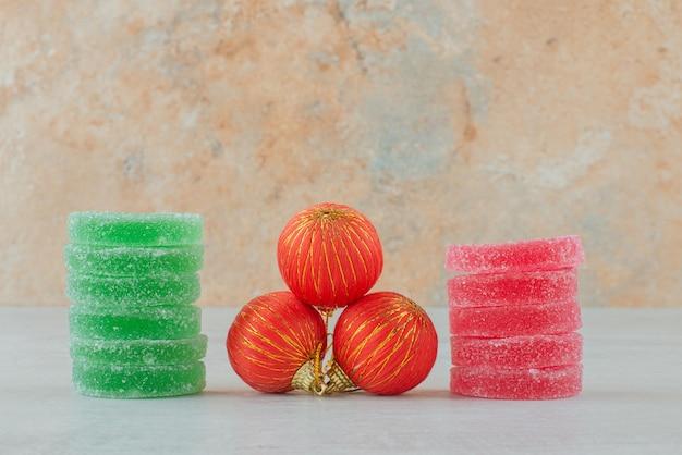 Marmelade aus grünem und rotem zucker mit roten weihnachtskugeln auf marmorhintergrund. hochwertiges foto
