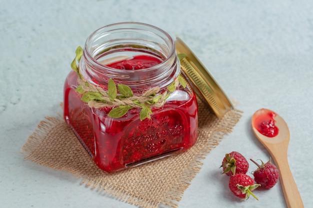 Marmelade im glas und himbeere auf dem boden über grauer oberfläche.