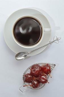 Marmelade in einer schüssel, einer tasse auf einer untertasse und einem löffel..