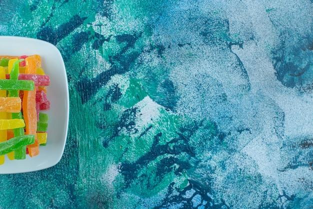 Marmelade in form von farbigen stäbchen in einer untertasse auf dem marmortisch.