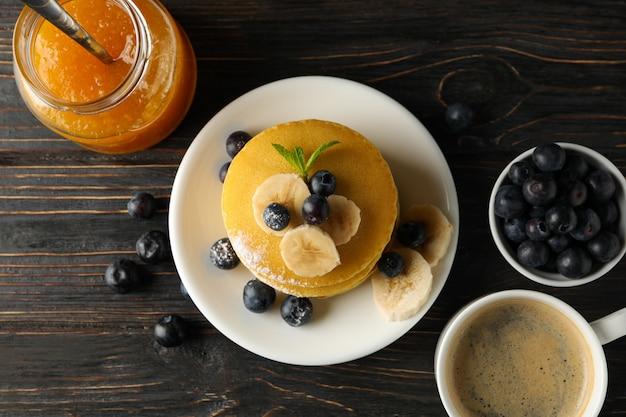 Marmelade, kaffee, pfannkuchen mit blaubeeren und bananen auf holzfläche