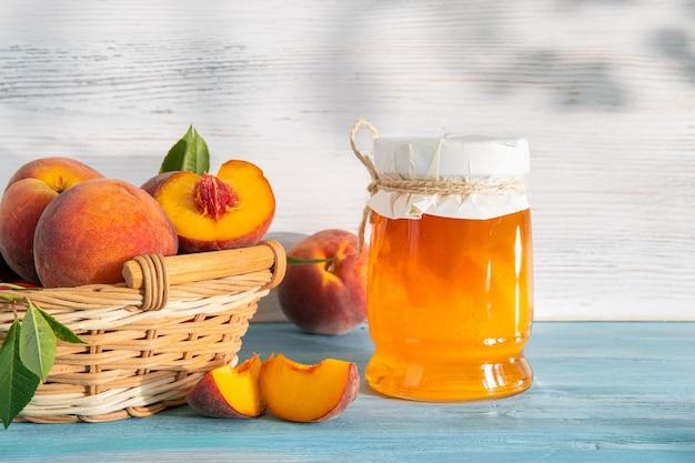 Marmelade und pfirsiche mit samen und blättern in einem weidenkorb
