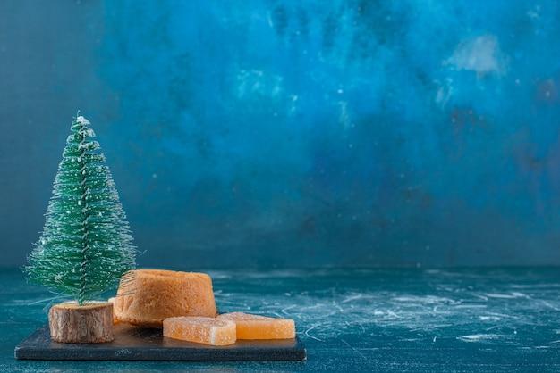 Marmeladen, ein kleiner kuchen und eine baumfigur auf einer schwarzen tafel auf blauem hintergrund. hochwertiges foto