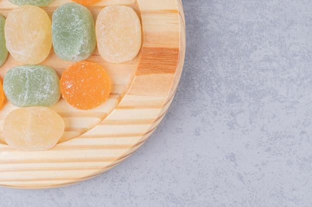 Marmeladen ordentlich auf einer holzplatte auf marmortisch angeordnet.