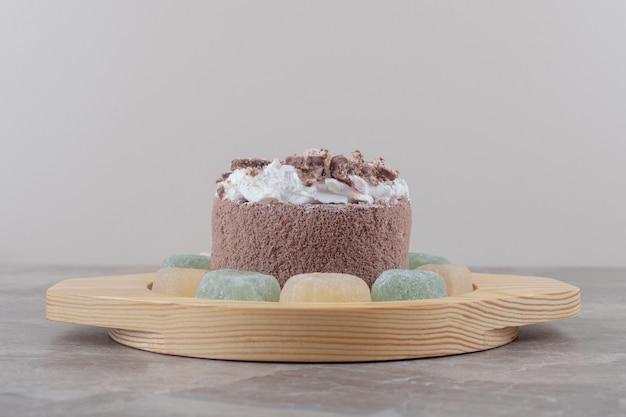 Marmeladen um einen kleinen kuchen auf einer holzplatte auf marmor