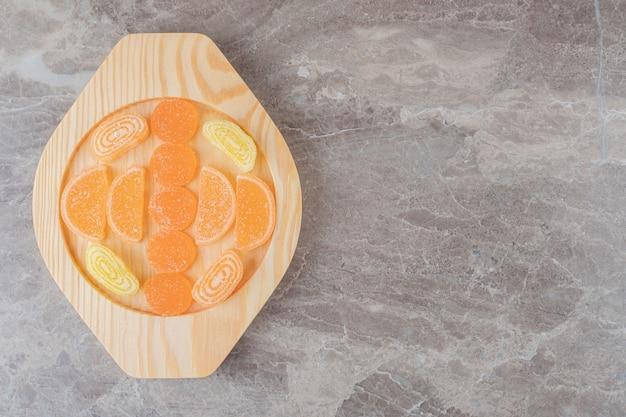 Marmeladenbündel auf einer holzplatte auf marmoroberfläche