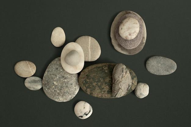 Marmor-zen-steine auf grünem hintergrund im gesundheits- und wellnesskonzept gestapelt