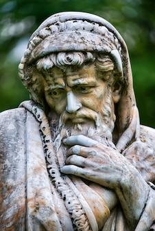 Marmorparkskulptur eines alten mannes, der gefriert und in bettdecken gewickelt ist, die die kalte jahreszeit verkörpern