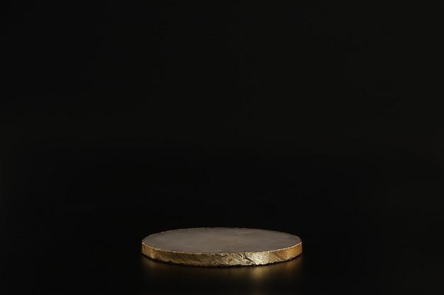 Marmorpodest mit gold auf schwarzem hintergrund. podium für produkt, kosmetische präsentation. kreatives mock-up. sockel oder plattform für schönheitsprodukte. minimalistisches design