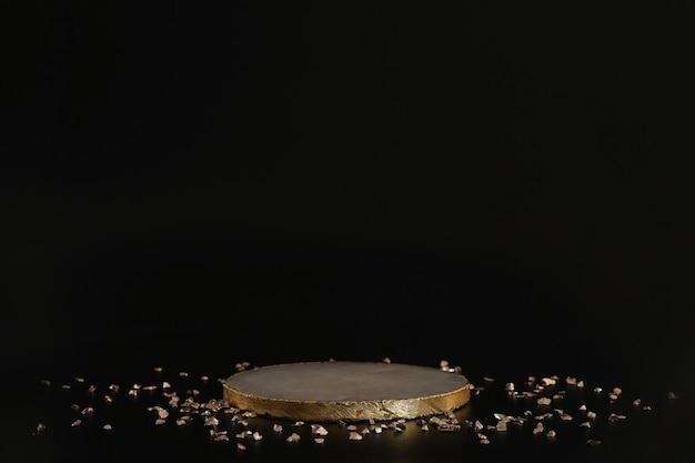 Marmorpodest mit gold und kleinen kristallen auf schwarzem hintergrund. podium für produkt, kosmetische präsentation. kreatives mock-up. sockel oder plattform für schönheitsprodukte. minimalistisches design