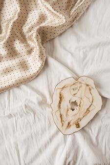 Marmortablett und seiden-polka-bot-stoff auf weißem leinen.