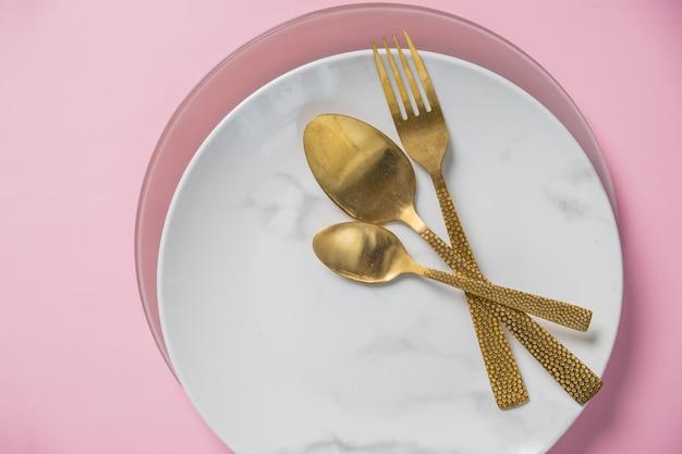 Marmorteller, goldmesser, gabel und löffel auf rosa wand. geschirr und besteck, teller mit löffeln und gabel. kunstdekor. abendessen, romantisches liebesessen und liebeskochkonzept.
