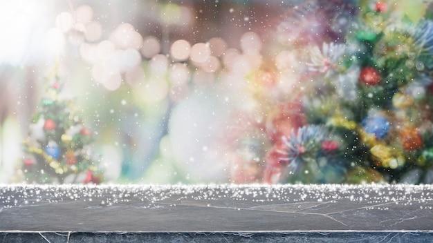 Marmortischplatte und verschwommene lichter mit weihnachtsbaum