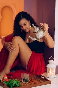 Marokkanische frau, die traditionellen arabischen tee zu hause vorbereitet