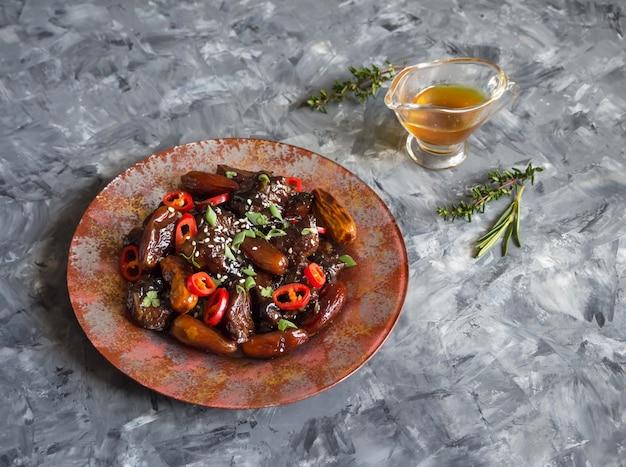 Marokkanische rindfleisch-tajine mit dattelsauce. knuspriges rindfleisch in süßer und klebriger sauce.