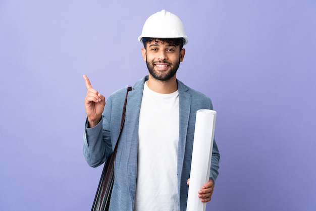 Marokkanischer mann des jungen architekten mit helm und hält blaupausen über isolierter wand, die eine idee denkt, die den finger nach oben zeigt