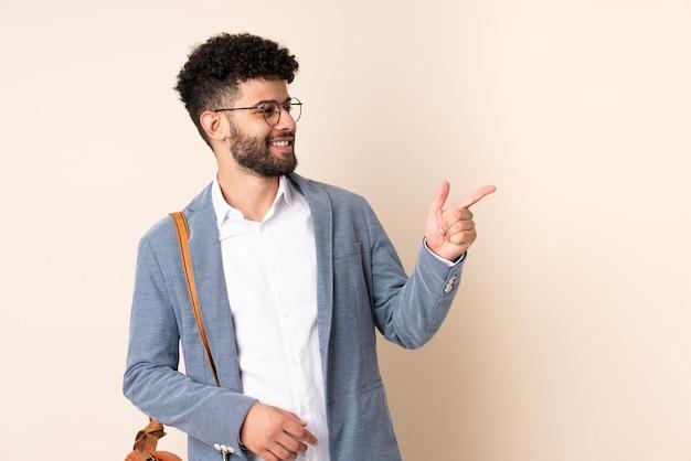 Marokkanischer mann des jungen geschäfts lokalisiert auf beige wand, die finger zur seite zeigt und ein produkt präsentiert