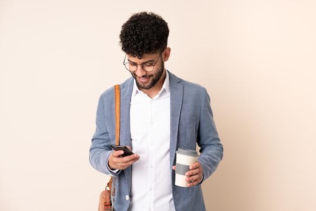Marokkanischer mann des jungen geschäfts lokalisiert auf beige wand, die kaffee hält, um und ein handy wegzunehmen