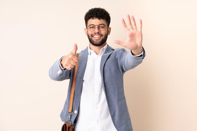 Marokkanischer mann des jungen geschäfts lokalisiert auf beige wand, die sechs mit den fingern zählt