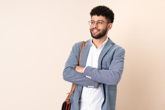 Marokkanischer mann des jungen geschäfts lokalisiert auf beige wand glücklich und lächelnd