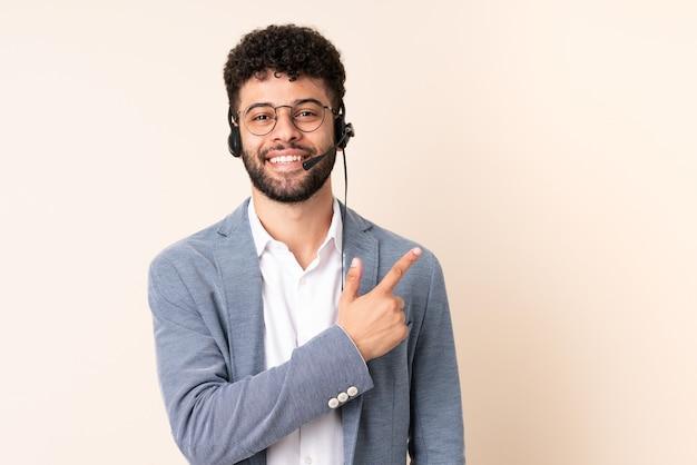 Marokkanischer mann des telemarketers, der mit einem headset arbeitet, das auf beigem hintergrund lokalisiert wird, der zur seite zeigt, um ein produkt zu präsentieren