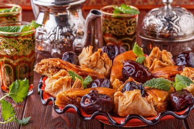 Marokkanischer minztee in den traditionellen gläsern mit süßigkeiten