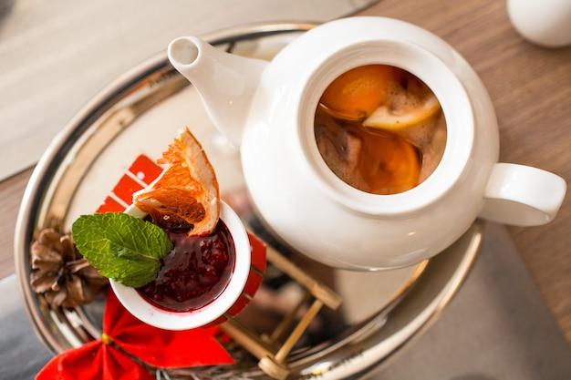 Marokkanischer tee mit orange und zitrone in einer teekanne mit himbeermarmelade und gewürzen