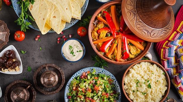 Marokkanisches essen. traditionelle tajine-gerichte, couscous und frischer salat auf rustikalem holztisch. tajine hühnerfleisch und gemüse. arabische küche. ansicht von oben. flach liegen