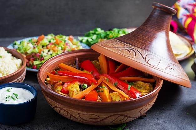 Marokkanisches essen. traditionelle tajine-gerichte, couscous und frischer salat auf rustikalem holztisch. tajine hühnerfleisch und gemüse. arabische küche.